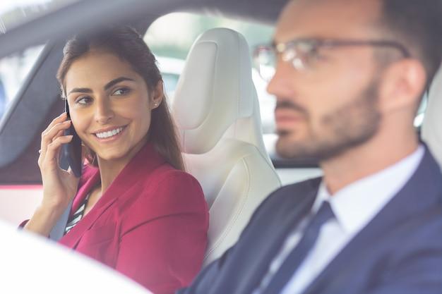 Сияющая жена. сияющая темноволосая любящая жена смотрит на своего красивого мужа за рулем машины