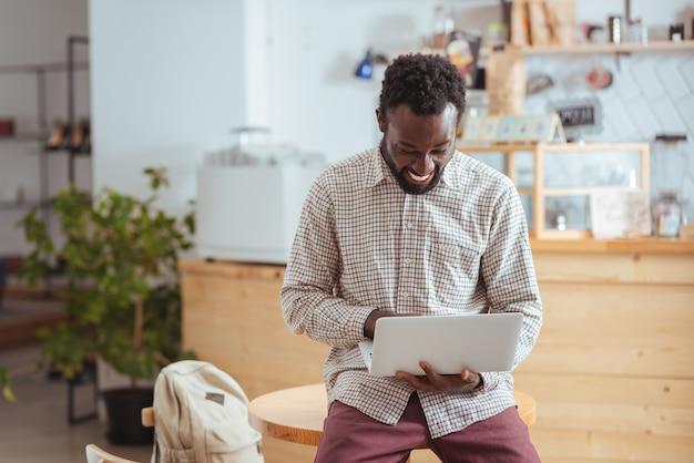 Сияющий от счастья. жизнерадостный молодой человек сидит на столе в кафе и работает за ноутбуком, широко улыбаясь и счастливо улыбаясь