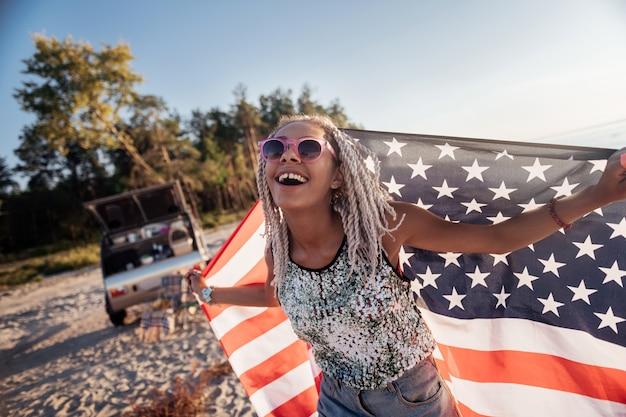 Сияющая женщина. сияющая улыбающаяся женщина с дредами держит флаг америки во время путешествия