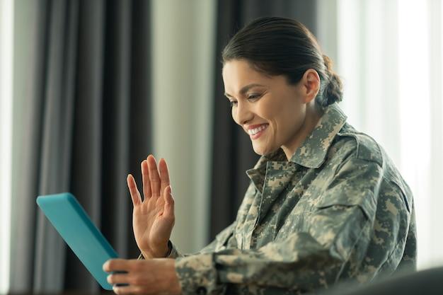 晴れやかな女性。子供たちとビデオチャットをしながら手を振っている軍隊で奉仕する晴れやかな女性