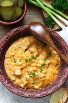 Тушеная фасоль и мясо, подается с солеными огурцами, хлебом и чесноком. деревенский стиль
