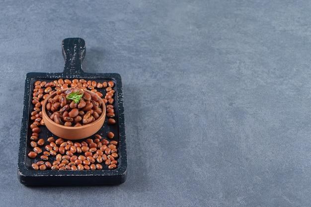 青い背景の上の豆ボード上の豆丼。