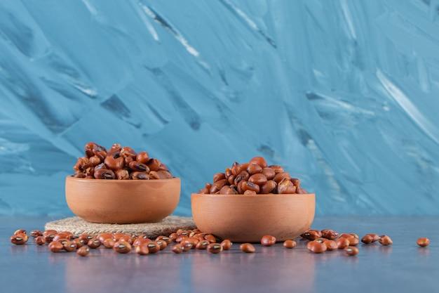 青い背景に、豆のボウルとトリベット。