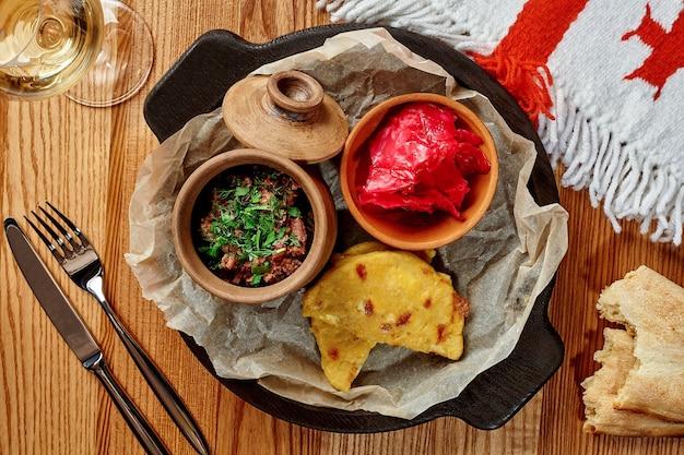 木製のテーブルにクルミのピクルス赤キャベツと揚げスルグニと豆のロビオ