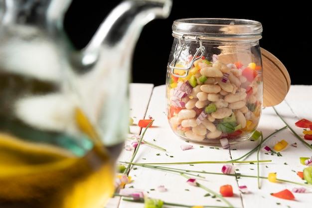 瓶とオイルブラックの背景に豆サラダミックス