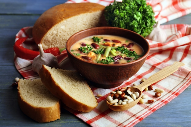 Bean soup in bowl with fresh sliced bread on napkin, on wooden table