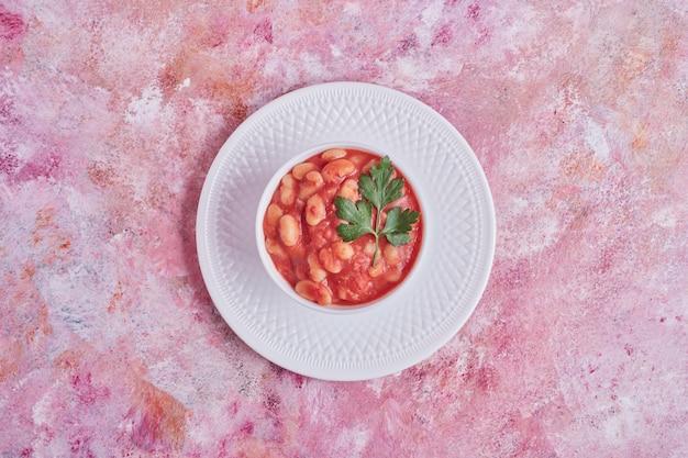 白いプレートのトマトソースの豆のスープ、上面図。