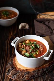 Фасолевый суп с мясом и овощами подается на деревенской доске и деревянном столе с хлебом и чесноком. традиционный балканский суп пасулдж (грах). крупный план, выборочный фокус