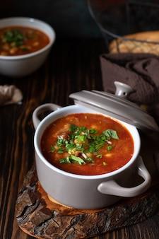 素朴な板とパンとニンニクの木製テーブルで肉と野菜を添えた豆のスープ。伝統的なバルカンスープpasulj(グラ)。クローズアップ、セレクティブフォーカス