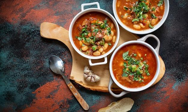 にんにくを添えた素朴なボードに肉と野菜を添えた豆のスープ。伝統的なバルカンスープまたはシチューcorbastpasulj(グラ)。上面図、コピースペース