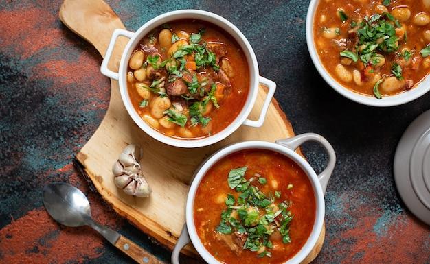 Фасолевый суп с мясом и овощами подается на деревенской доске с чесноком. традиционный балканский суп или рагу корбаст пасулдж (грах). вид сверху, копировать пространство