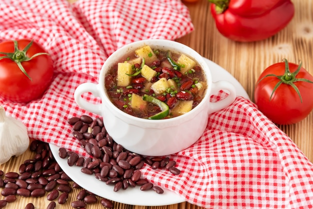 Bean soup with meat in a white ceramic bowl.