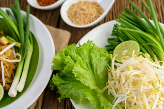 Bean sprouts, salads, lime and spring onions in white plate on wooden table