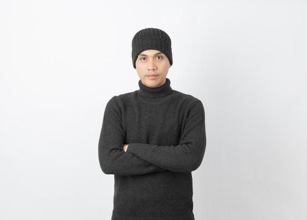 Молодой азиатский человек нося серые свитер и beanie пока смотрящ к камере с счастливым лицом на белизне