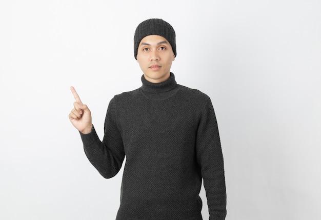 Молодой красивый азиатский человек нося серый свитер и beanie указывая к стороне с пальцами для того чтобы представить продукт или идею на белизне
