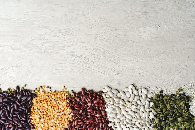 Beans assortment on white stone table, close up.