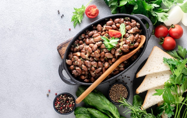 Beans baked in white sauce with spinach in a black bowl