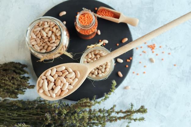 Фасоль, нут, чечевица и сухие травы на кухонном столе, органические натуральные продукты