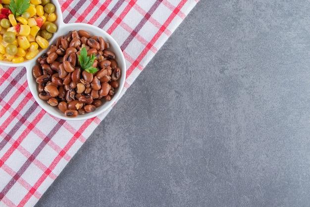 Fagioli e insalata di mais su un piatto su un asciugamano, sullo sfondo blu.