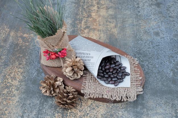 木の板に松ぼっくりと新聞の豆。高品質の写真