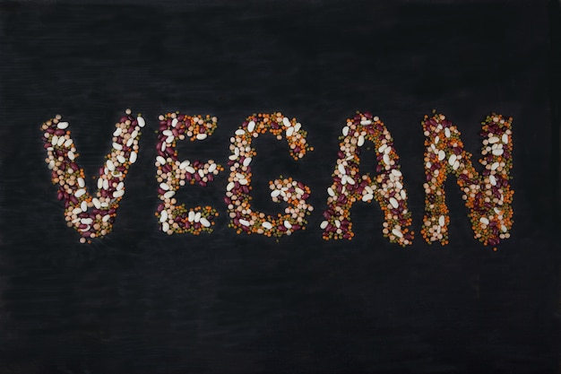 Beans, lentils, mung bean, peas laid out on a black wooden background in the form of the inscription vegan