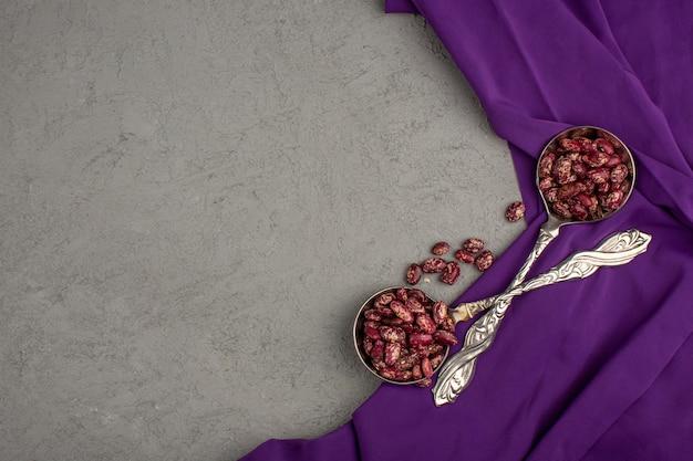Фасоль костного мозга свежая сырая на пурпурной ткани и серая