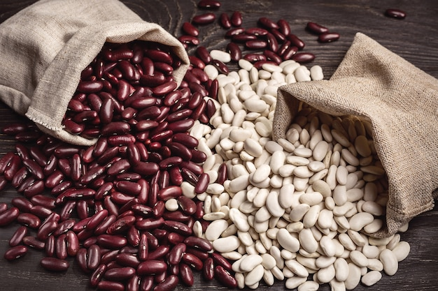Beans red and white in bags on dark wooden table.
