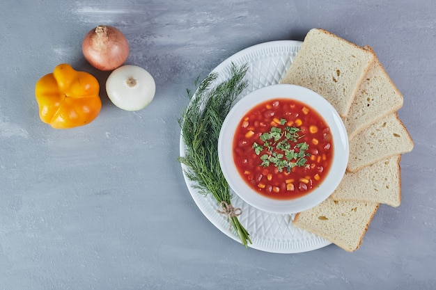 Beans soup in tomato sauce with bread slices and herbs.