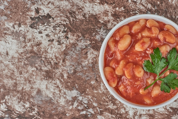 Beans soup in tomato sauce .