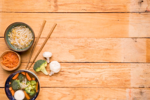 Beans sprout; carrot; and fish ball soup with chopsticks on wooden table