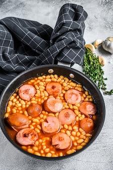 鍋にトマトソースのソーセージと豆