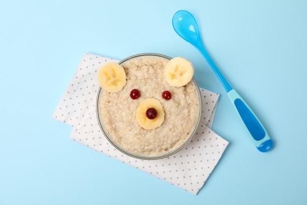 Принесите лицо сделанное из каши и плодоовощей на голубой предпосылке, взгляд сверху. детская еда