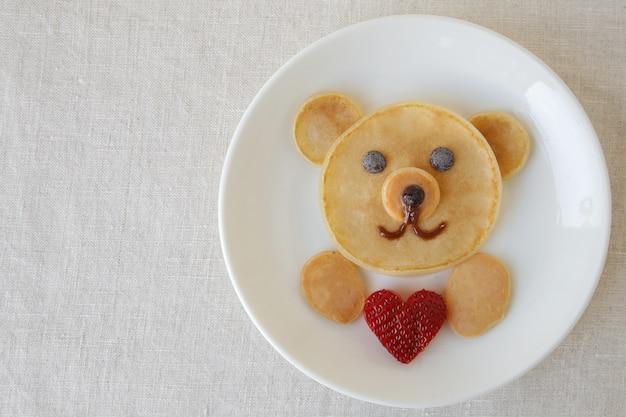 愛の心パンケーキ朝食、子供のための楽しいバレンタインフードアートを保持しているクマ