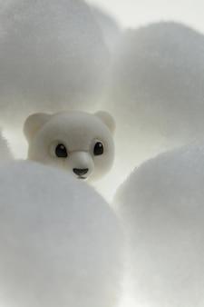 Медведь в снегу. игрушка белого медведя в белых помпонах.