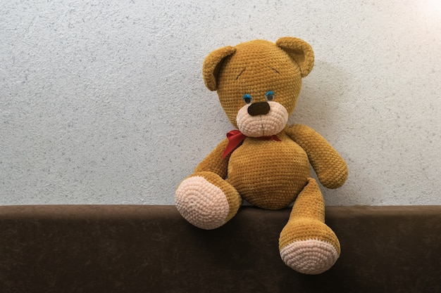 A bear sitting alone on the back of the sofa. beautiful knitted toy.