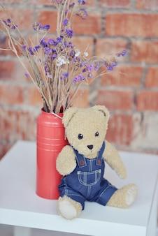 Медведь сидит на столе, возле букета цветов
