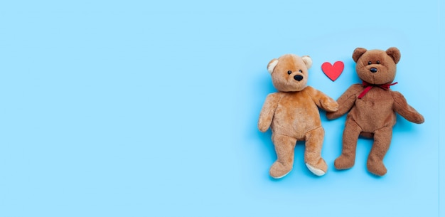 Bear toy couple with heart on blue background.