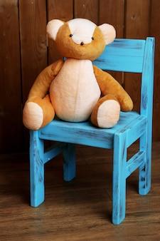 나무 배경에 의자에 곰 장난감