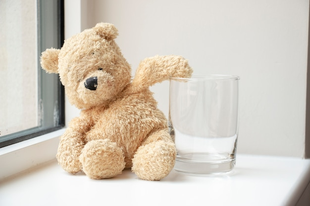 Bear with empty glass of water .