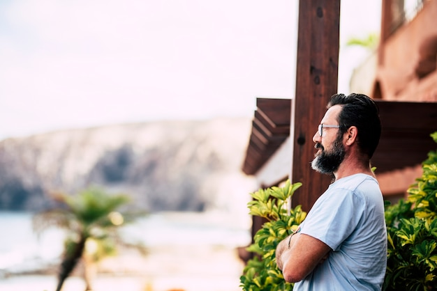 Борода взрослый кавказский постоянный мужчина смотрит на улицу дома