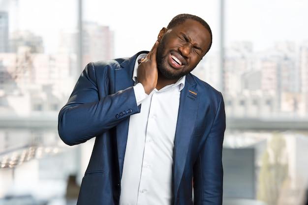 ひげのビジネスマンは首の痛みを感じます。首の痛みに苦しんでいる黒人実業家