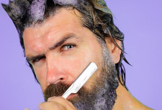 수염 관리. 수염난 남자는 면도기로 면도합니다. 이발소. 면도 남자의 초상화를 닫습니다.