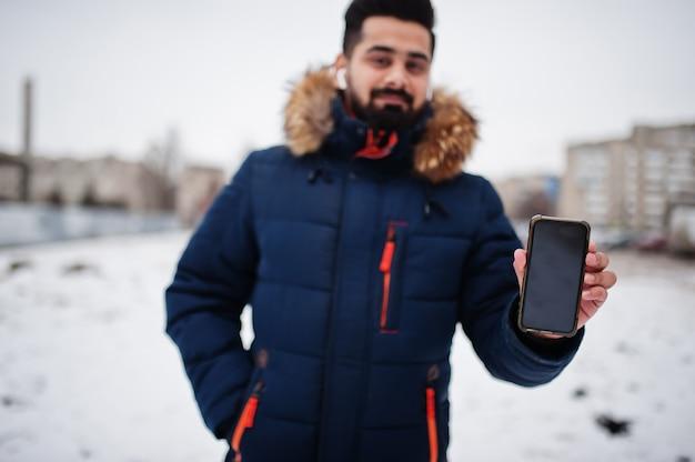 寒い冬の日にひげのインド人男性はジャケットを着ます。彼はワイヤレスヘッドホンで携帯電話を話します。