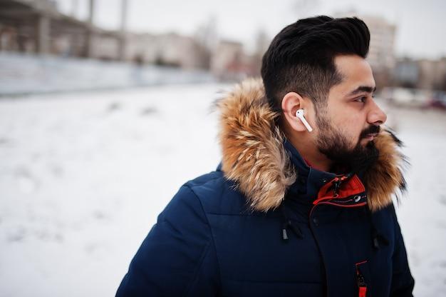 寒い冬の日にひげのインド人男性はジャケットを着ます。耳の中の携帯電話。