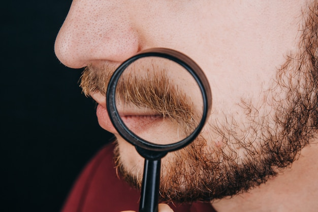 Beard under a magnifying glass. hairline on a man's face close up.