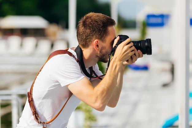 흰색 티셔츠에 수염 남자는 디지털 카메라에 사진을 만든다. 찬성