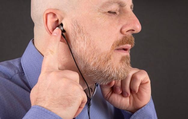 ヘッドフォンで音楽を聴くひげの男