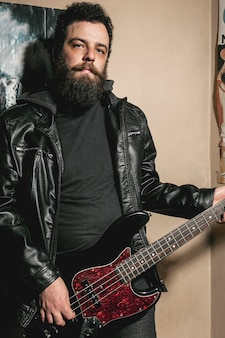 Beard man playing on bass guitar