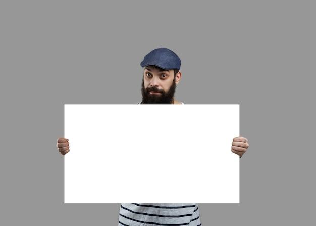 L'uomo con la barba in camicia tiene un foglio bianco di carta bianca per il prodotto incerto o il testo di vendita.