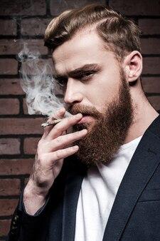 ひげの男喫煙。タバコを吸って、レンガの壁に立ってカメラを見ているハンサムな若いひげを生やした男